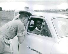 A policeman talking to a man siting inside the car in Rhodesia. Photo taken in November 1965.