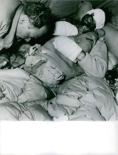 A man tending on a wounded man lying down and covered in plasters and bed sheets.