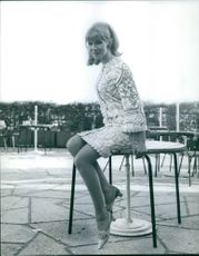 Susan Hampshire sitting on a table.
