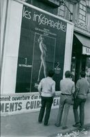 Men standing and looking at poster on roadside. 1970