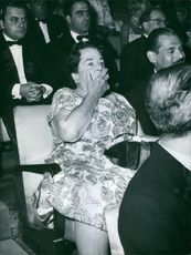 Elsa Maxwell covering her mouth. 1961.