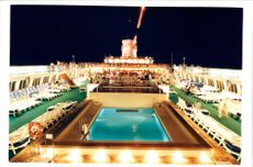 Crown Princess ship:young boys sits alone by pool.