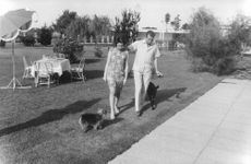 Juan Carlos I walking with a woman in his lawn.