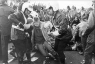 Protestors resist non-violently as police arrest them during a blockade of the Greenham Commons U.S. Air Force Base in England