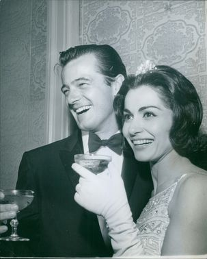 A MAN HAVING DRINK & SMILING WITH HER WIFE