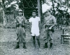 Soldiers standing together with a man in Netherlands New Guinea. Photo taken on May 28, 1962.