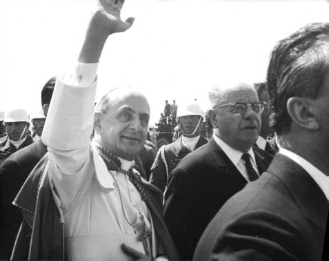 Pope Paul VI surrounded by the people waving at the crowd.