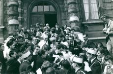 People gathered in front of building, man giving autograph.