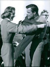 Hedwig Fischer, wife helping Toni Sailer put on his sweater. 1959.