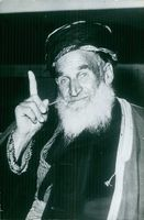 A photo of a bearded man pointing his finger upward.