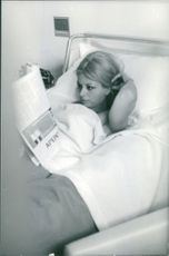Sandra Milo lying on bed and reading newspaper.