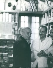 Georges Bidault talking to two men in a grocery store, smiling at the camera.  - Dec 1964