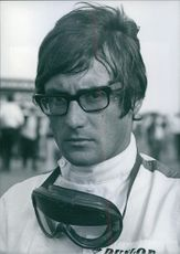 British racing driver Michael Keens wearing eyeglasses with goggles hanging over his neck, 1967.