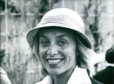 Woman standing and smiling. wearing a designed hat.