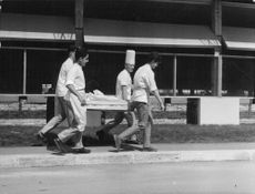 Four people carrying material.