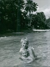 Martine Carol swimming with a child.