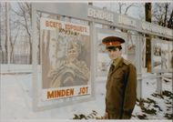 Soviet captain in front of a poster wishing the Hungarians good luck.