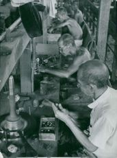 Old men working together in a factory.
