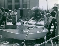 Rosalind Russell practicing handling a row boat between scenes of her current film.