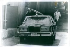 Steven Seagal is lying down above a car in a scene of the film, Above the Law(Nico). 1988