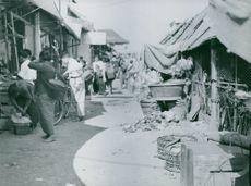 Locals scattered in a narrow road an in Indonesian Town, Indonesia.