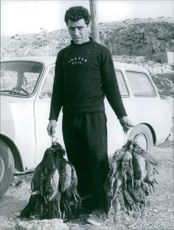 Man standing beside the car and holding Pheasants. Photo taken on January 27, 1966.