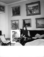 Ludmilla Tcherina sitting on a couch, showcasing a painting.