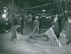 Men placing a carpet on the road with buntings hanged in the area, 1960.