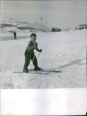 A little boy skiing on the ice.