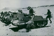 Soldiers getting into the military tanks during wartime.