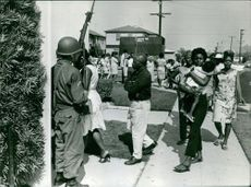 People lining up an entering a guarded place in Los Angeles.
