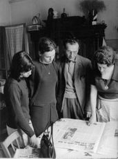 A FAMILY LOOKING AT THE NEWSPAPER