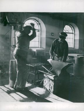 Arboga Mechanical Workshop. At the forge in the smithy, the old smith G. A. Wengson stands up and holds up when his beggar slows