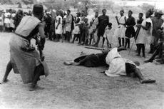 Two men brawling on the ground for a competition as the crowd watch.