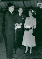 King Gustaf VI Adolf talks with Queen Elizabeth at the big flower show in Chelsea.