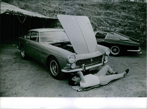 Portrait of  a French singer from Cairo, Egypt Richard Anthony lying under his car and repairing. 1964