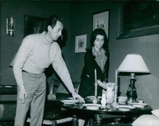 Prince Xavier helping a woman to manage dining table and smiling.1965