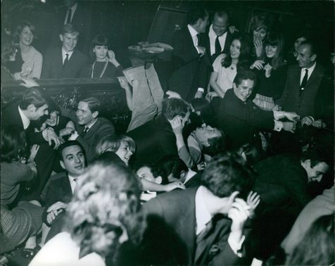 Crowd having fun at a party. 1965.
