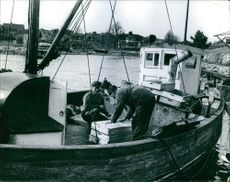 Man working, another man helping him in boat.