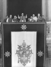 Pope Paul VI standing in the balcony with people.