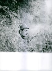 A soldier hiding in a field of grass during the France war, 1963.