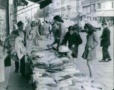 1967  A photo of people gathered and buying garments from shop at roadside.
