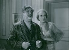 """In the film """"Bröllopsresan """"(1936), Erik 'Bullen' Berglund with shaving creme on his face while Anne-Marie Brunius stood beside him and they both look on same direction."""