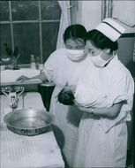 Two nurses bathing the baby's head.