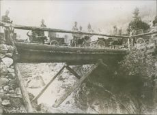 Soldiers crossing their supplies on a bridge using their dogs to pull the carts. They are from the armies of Eastern allies.