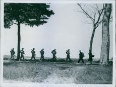 A line of British soldiers in a file pushing through while Belgian refugees are seen passing them. 1940.