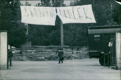 Uniformed man walking on area with a hanged banner.