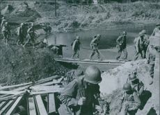 U.S. infantrymen file across an improvised footbridge over a Canal in Holland.