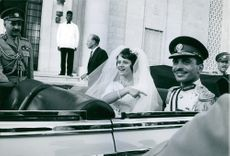 King Hussein and his bride Princess Muna al-Hussein riding an open-top car at their wedding parade.