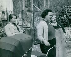 Three women standing with baby cart, looking at something.
